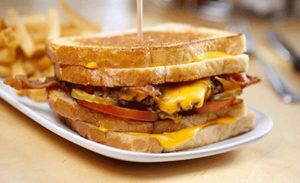 bacon cheeseburger, tomato, pickle, ketchup, between two grilled cheese sandwiches