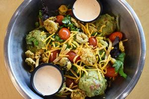 mixed greens, guacamole, tomato, cheddar, cilantro, jalapeño bottle caps, tortilla strips