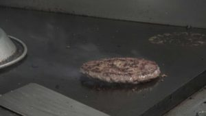 burger frying on grill