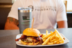 A Special Forces cup setting next to a crave real burger