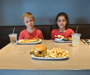 Two children enjoying a tasty burger and fries