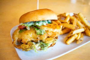 Hawaian inspired chicken sandwhich with fries