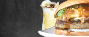 Home page burger and shake menu image, containing a caramel, banana, pudding shake and a hearty onion ring burger